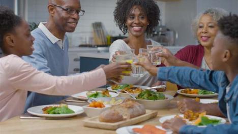 Familia-Juntando-Sus-Vasos-Saludando-Antes-De-La-Cena