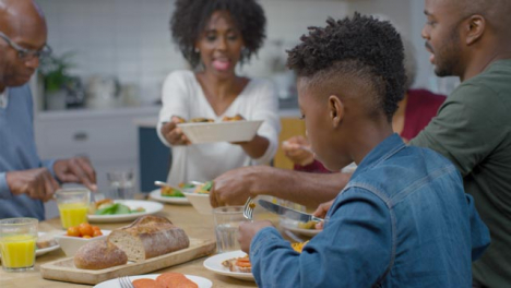 Family-Begin-Plating-Up-and-Eating-Evening-Dinner-Together-
