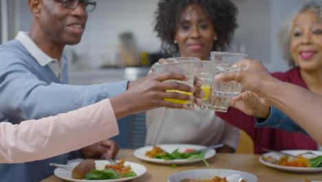 Familia-Juntando-Sus-Vasos-Diciendo-Salud-Antes-De-La-Comida