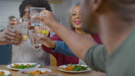 Familia-Juntando-Sus-Bebidas-Diciendo-Salud-Antes-De-La-Comida