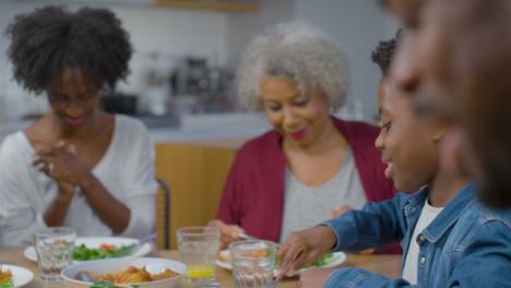 Familia-Hablando-Y-Riendo-Mientras-Cenan-Juntos