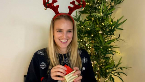 Young-Woman-On-Christmas-Video-Call-Opening-a-Present-Whilst-Talking-to-Camera