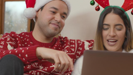 Rising-Close-Up-of-Couple-Talking-Into-Laptop-During-a-Christmas-Video-Call