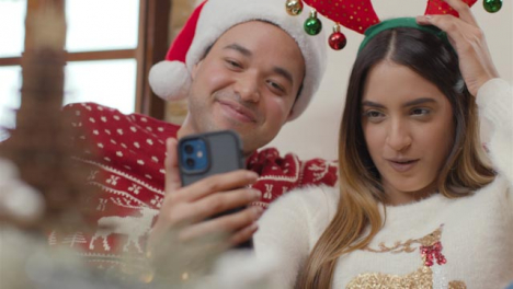 Pull-Focus-Shot-of-Couple-Talking-Into-Phone-During-Christmas-Video-Call