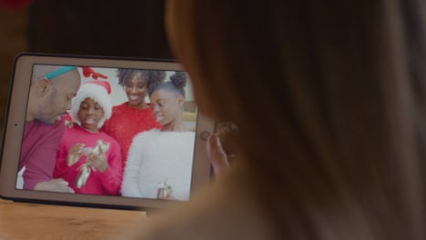 Over-the-Shoulder-Shot-of-Woman-Talking-to-Family-During-Christmas-Video-Call