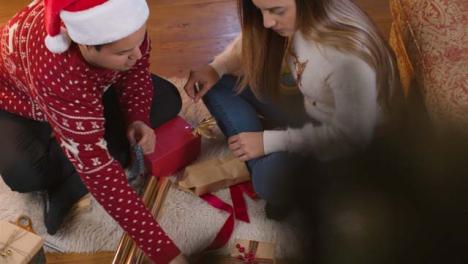 High-Angle-Shot-of-Couple-Wrapping-Up-Christmas-Present-Together