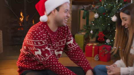 Tracking-Shot-Through-Stair-Rails-of-Young-Couple-Wrapping-Christmas-Present