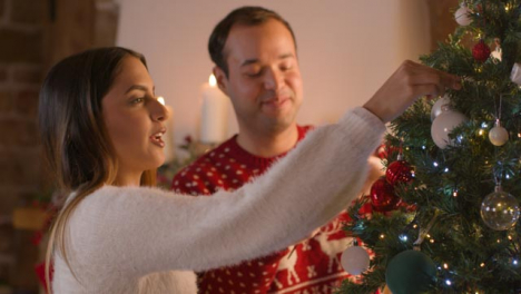 Medium-Shot-of-Young-Couple-Decorating-Christmas-Tree-Together