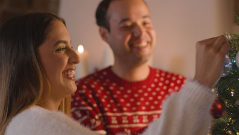 Close-Up-Shot-of-Young-Couple-Decorating-a-Christmas-Tree-Together