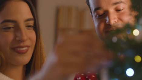 Close-Up-Shot-of-Young-Couple-Decorating-Their-Christmas-Tree-Together