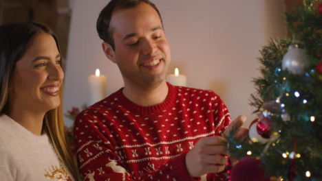 Medium-Shot-of-a-Young-Couple-Decorating-a-Christmas-Tree-Together