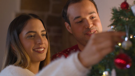 Close-Up-Shot-of-Joyful-Young-Couple-Decorating-Christmas-Tree-Together