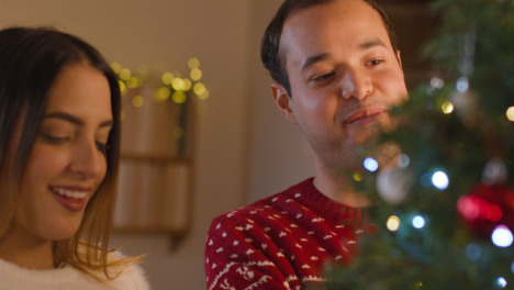 Tracking-Shot-From-Behind-Christmas-Tree-As-Young-Couple-Decorate-It-Together