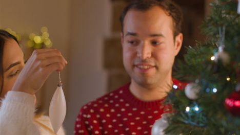 Tracking-Shot-From-Behind-a-Christmas-Tree-As-Young-Couple-Decorate-It-Together