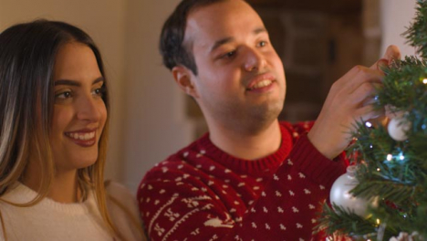 Close-Up-Shot-of-a-Joyful-Young-Couple-Decorating-Christmas-Tree-Together