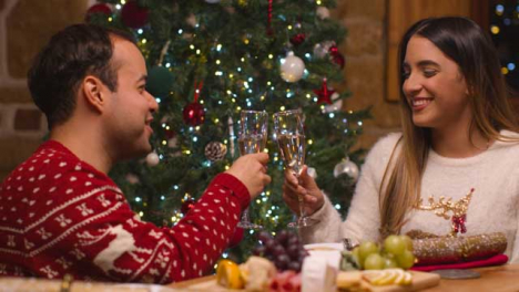 Medium-Shot-of-Couple-Bringing-Their-Champagne-Glasses-Together-Before-Pulling-Christmas-Cracker