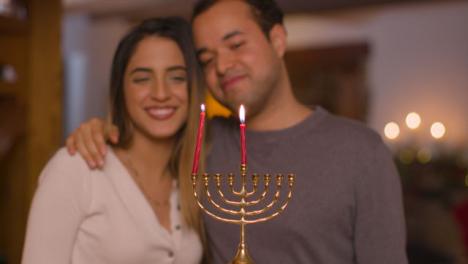 Plano-Medio-De-Una-Pareja-Joven-Encendiendo-La-Primera-Vela-De-La-Menorá-Durante-Hanukkah