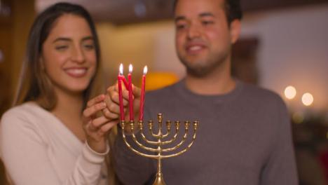 Plano-Medio-De-La-Joven-Pareja-Encendiendo-Tres-Velas-De-Menorá-Durante-Hanukkah