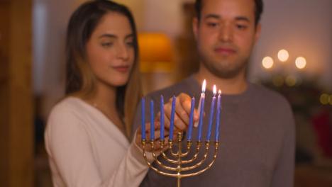 Plano-Medio-De-La-Joven-Pareja-Encendiendo-Velas-En-La-Menorá-Durante-Hanukkah