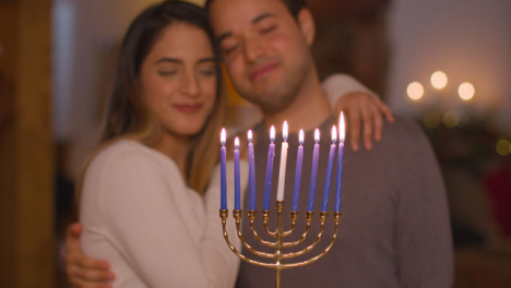 Medium-Shot-of-Young-Couple-Lighting-Candles-On-Menorah-During-Hanukkah-Celebration
