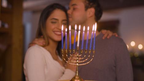 Medium-Shot-of-Young-Couple-Looking-at-Burning-Candles-On-Menorah-During-Hanukkah