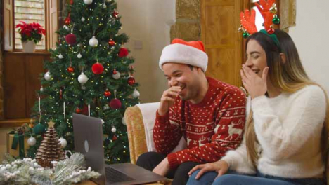 Wide-Shot-of-Young-Couple-Laughing-and-Talking-to-Laptop-Camera-During-Christmas-Video-Call-