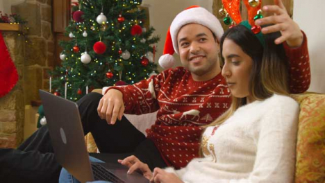 Medium-Shot-of-Young-Couple-Talking-to-Laptop-Webcam-During-a-Christmas-Video-Call-