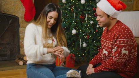 Sliding-Shot-of-Young-Woman-Trying-On-Bracelet-Given-to-Her-for-Christmas-by-Boyfriend