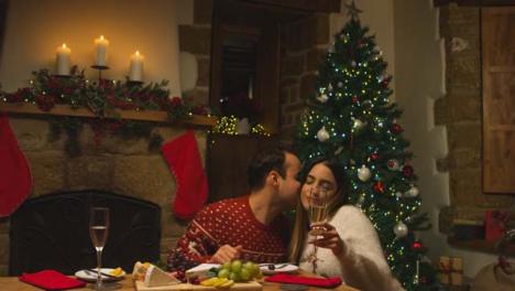 Sliding-Medium-Shot-Approaching-Young-Man-Kissing-His-Girlfriends-Cheek-During-Christmas