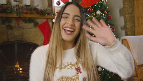 Young-Woman-Waving-and-Talking-to-Camera-During-Christmas-Video-Call