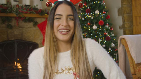 Young-Woman-Talking-and-Laughing-to-Camera-During-Christmas-Video-Call