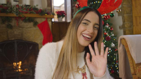 Young-Woman-Talking-and-Waving-to-Camera-During-Christmas-Video-Call