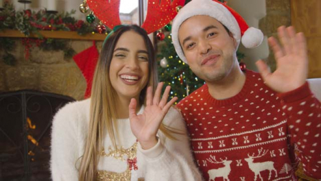 Young-Couple-Waving-and-Talking-to-Camera-During-Christmas-Video-Call-