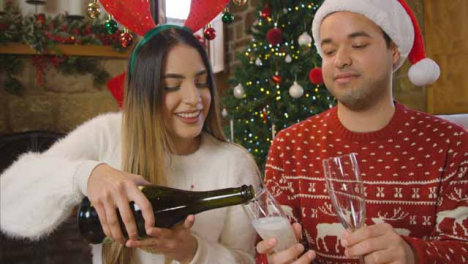 Young-Couple-Opening-a-Bottle-of-Champagne-During-Christmas-Video-Call