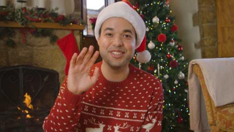 Young-Man-Waving-and-Talking-to-Camera-During-Christmas-Video-Call