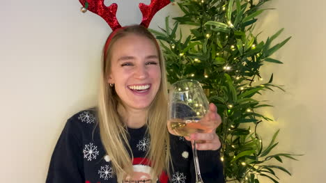 Young-Woman-On-Christmas-Video-Call-Playfully-Raising-Her-Glass-to-Camera
