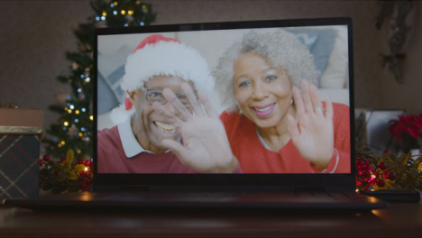 Close-Up-Shot-of-Senior-Couple-During-Video-Call-On-Laptop-Screen-In-Christmas-Environment