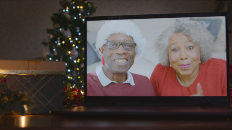 Sliding-Close-Up-Shot-of-Senior-Couple-During-Video-Call-On-Laptop-Screen-In-Christmas-Environment