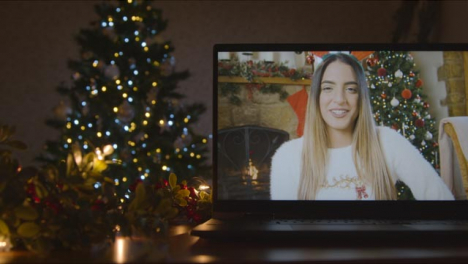 Sliding-Close-Up-Shot-of-Young-Woman-During-Video-Call-On-Laptop-Screen-In-Christmas-Environment