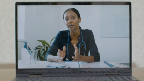 Sliding-Medium-Shot-of-Laptop-Screen-with-Doctor-On-a-Video-Call