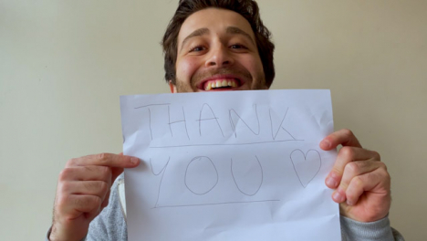 Young-Male-University-Student-Holding-Up-Thank-You-Sign-During-Video-Lecture