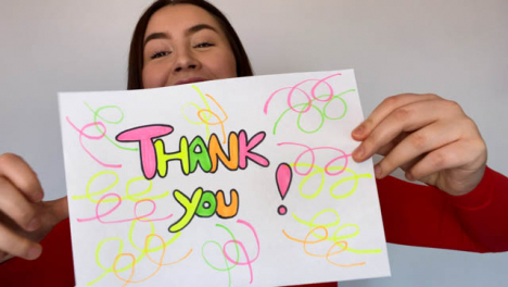 Young-Female-Student-Holding-Up-Thank-You-Sign-During-Video-Lecture