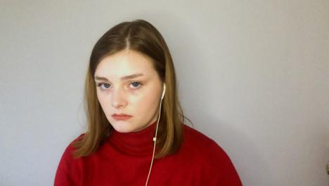 Joven-Estudiante-Visiblemente-Aburrida-Mientras-Mira-Directamente-A-La-Cámara-Durante-Una-Conferencia-Remota