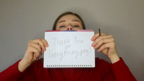 Female-Young-Student-Holding-Up-Thank-You-Sign-During-Video-Lecture