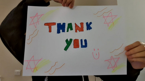 Older-Student-Holding-Up-Thank-You-Sign-During-Video-Lecture