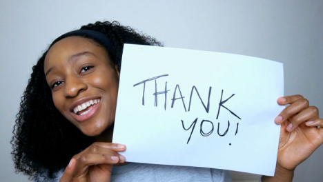 Young-Student-Holding-Up-Thank-You-Sign-During-Video-Lecture