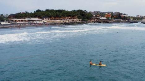 Drone-Shot-Orbiting-Two-People-Sitting-On-Surf-Board-In-Ocean
