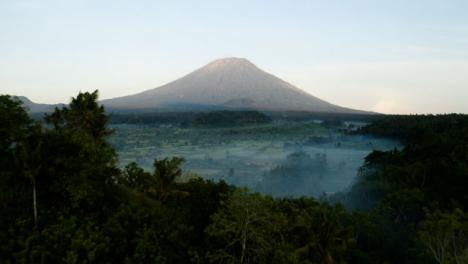 Disparo-De-Drone-Volando-Sobre-Los-árboles-Hacia-El-Volcán-Monte-Agung
