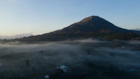 Drone-Shot-Ascending-Over-Low-Hanging-Mist-Around-Mount-Batur-Volcano