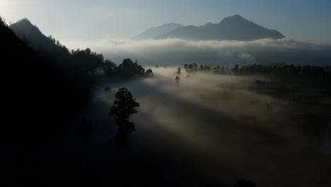 Drone-Shot-Passing-Over-Low-Hanging-Mist-Surrounding-Mount-Batur-